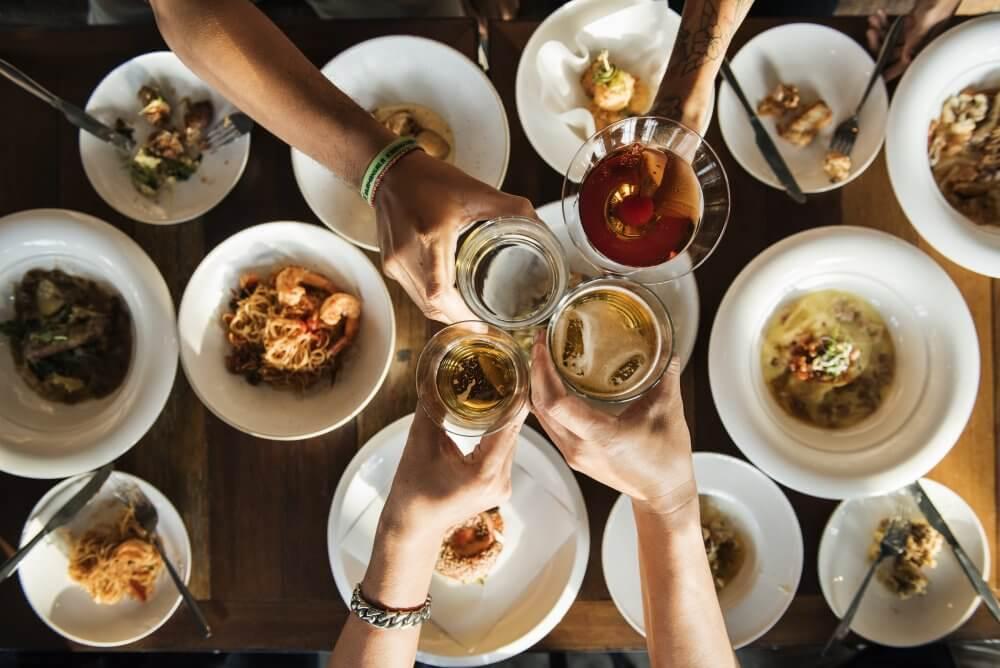 Dinner table food drinks friends cheering